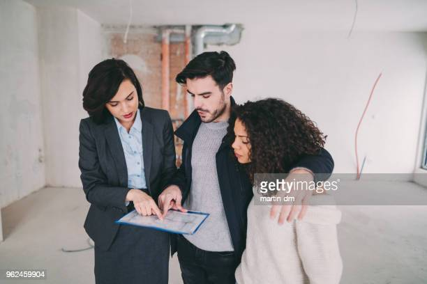 real estate agent showing condo for sale to young couple - visita imagens e fotografias de stock