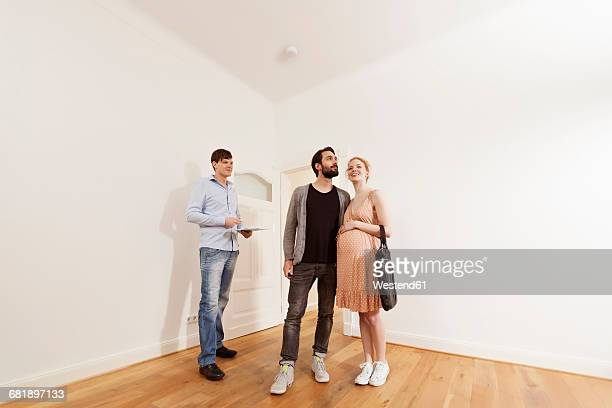 Real estate agent showing expecting parents around in a new apartment