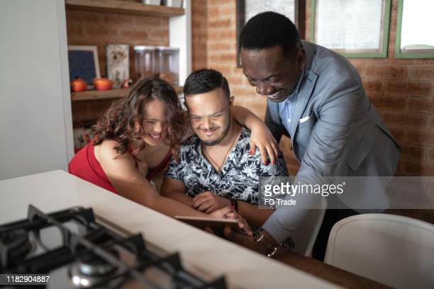 real estate agent showing house information to a special needs couple, sitting in the kitchen table - persons with disabilities stock pictures, royalty-free photos & images