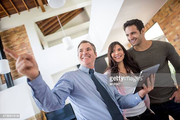 real estate agent showing house to a couple - showing stock photos and pictures