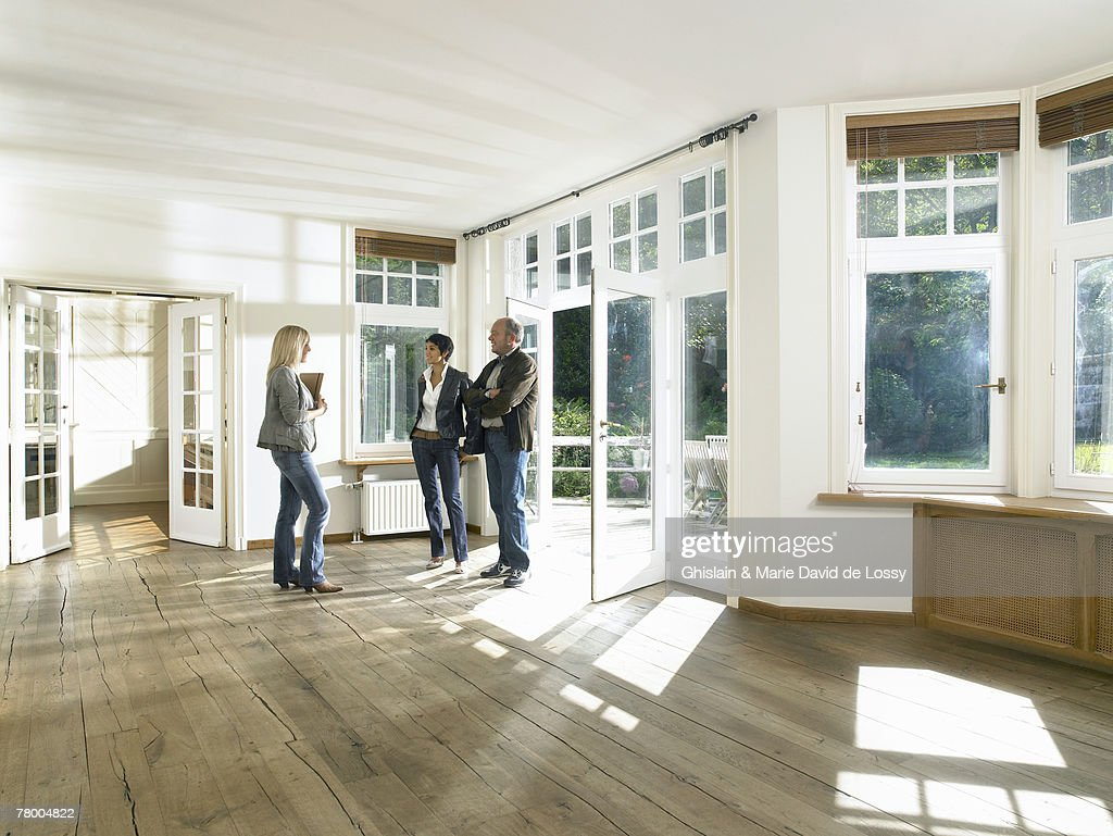 Real estate agent showing house to a couple. : Stock Photo