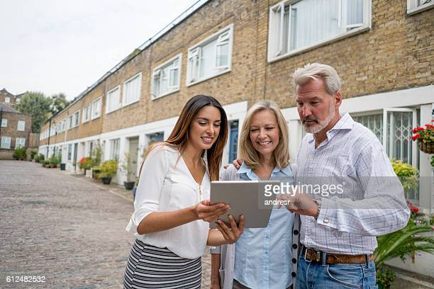 Real estate agent showing houses to a couple