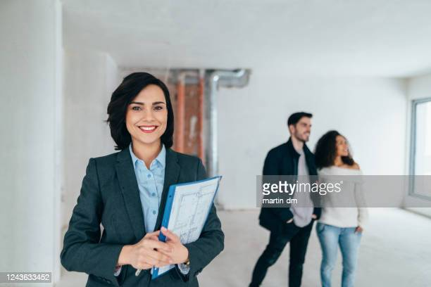 real estate agent showing new home to clients - real estate agent stock pictures, royalty-free photos & images