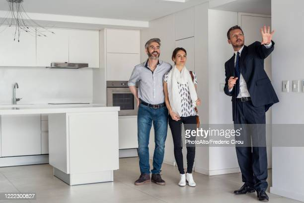 real estate agent showing new house to couple - real estate agent stock pictures, royalty-free photos & images