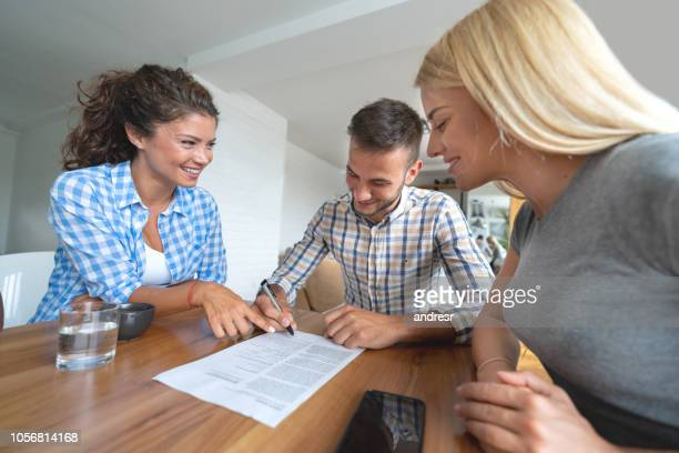 real estate agent signing a contract with a couple - lease agreement stock photos and pictures