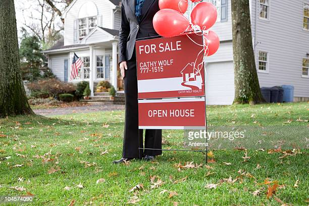 A real estate agent standing by a FOR SALE sign