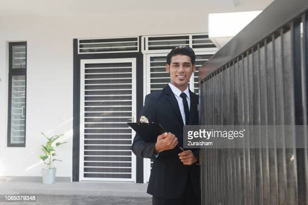 a real estate agent stands in front of a house for sale in kuala lumpur, malaysia - real estate developer stock pictures, royalty-free photos & images