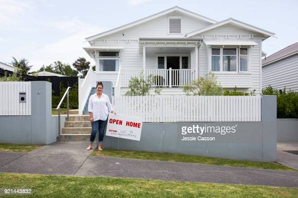 Real estate agent stands next to For Sale sign in front of white traditional villa