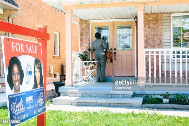 A real estate agent stands outside of a home holding an open house in Brampton Ontario Canada on Saturday May 20 2017 After a double whammy...
