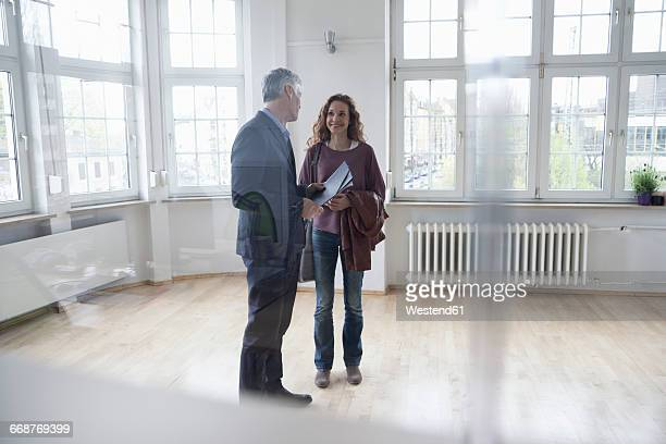 Real estate agent talking to client in empty apartment