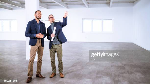 real estate agent talking to entrepreneur in an empty office building - real estate stock pictures, royalty-free photos & images