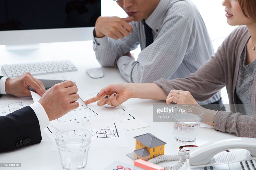 Real estate agent to show a blueprint to couple stock photo getty real estate agent to show a blueprint to couple stock photo malvernweather Images