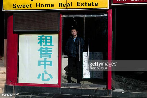 A real estate agent waits for customers inside his office in Beijing on January 17 2016 China recorded its lowest growth in a quarter of a century in...