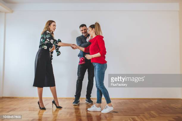real estate agent welcoming a family in to a new home - selling stock pictures, royalty-free photos & images