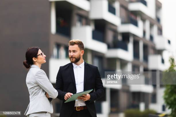 real estate agent with a client - real estate stock pictures, royalty-free photos & images
