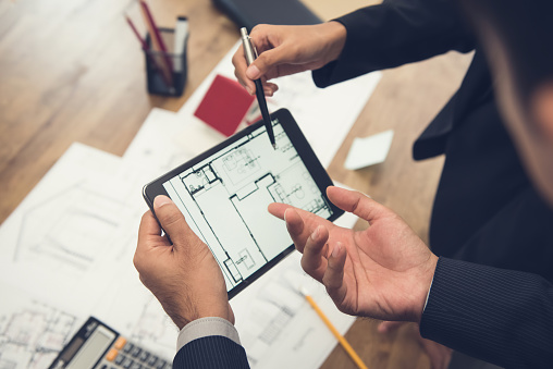 Real estate agent with client or architect team checking a housing model and its blueprints digitally using a tablet 952643774
