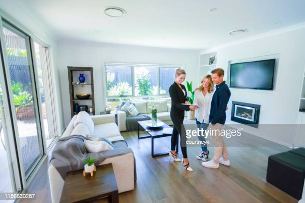 real estate agent with couple in luxury home. - real estate stock pictures, royalty-free photos & images