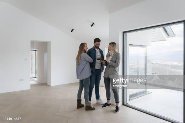 immobilienmakler mit paar in luxus-haus - kaufen stock-fotos und bilder