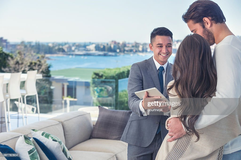 Real estate agent with couple in luxury home. : Stock Photo