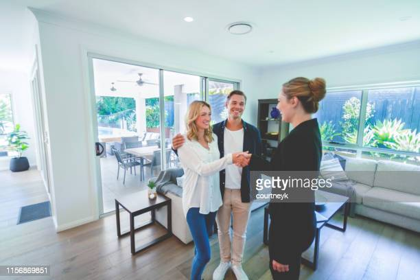 real estate agent with couple in luxury home. they are shaking hands. - real estate stock pictures, royalty-free photos & images