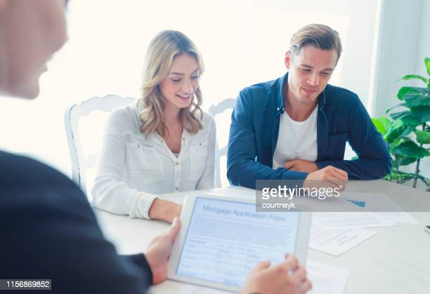 real estate agent with couple looking through documents. - real estate stock pictures, royalty-free photos & images