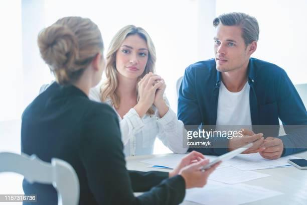 agente de bienes raíces con pareja mirando documentos. - abogado fotografías e imágenes de stock