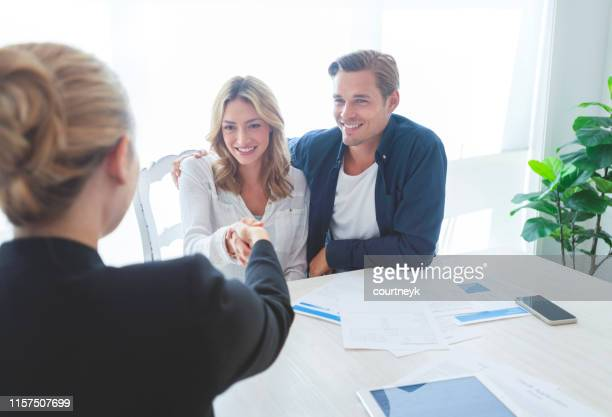 real estate agent with couple shaking hands closing a deal. - closing stock pictures, royalty-free photos & images