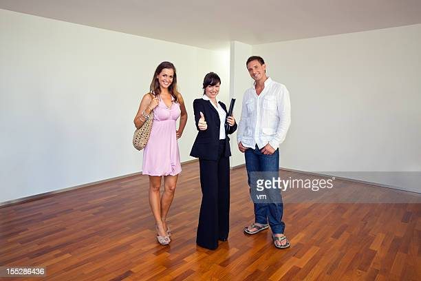 Real estate agent with customers looking at camera