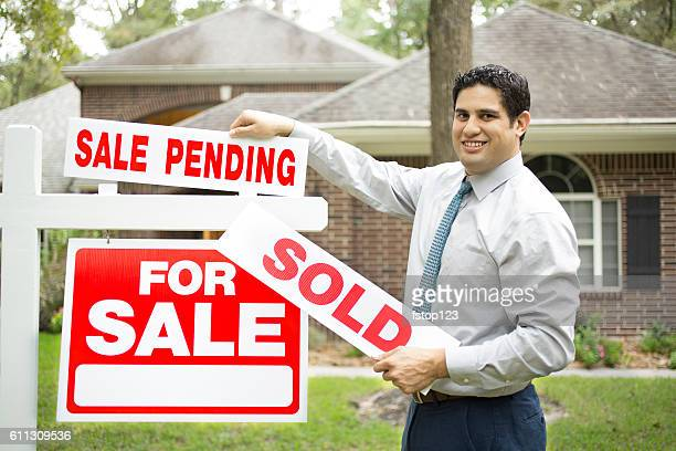 Real estate agent with home for sale, sold sign.