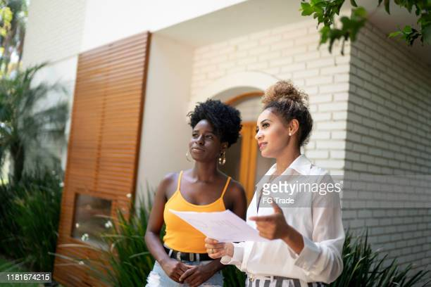 real estate agent/financial advisor talking to a client in front of a house - real estate agent stock pictures, royalty-free photos & images