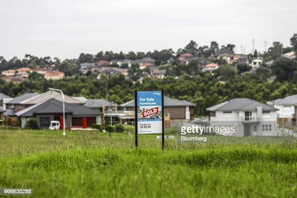 A real estate billboard with a 'sold' sign stands near newly constructed houses in the suburb of Kellyville in Sydney Australia on Thursday March 30...