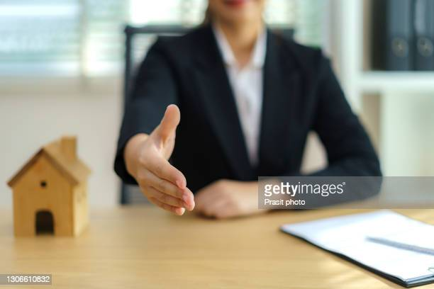 real estate broker businesswoman ready to shakehand to seal a deal with her customer signing a contract: real estate, home loan and insurance concept. - mortgage stock pictures, royalty-free photos & images