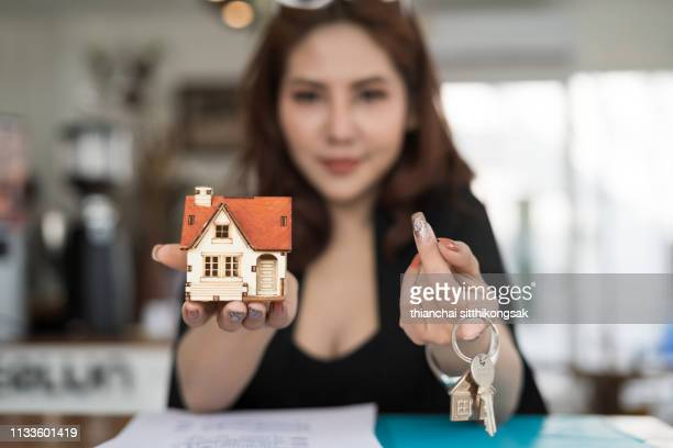 real estate concept; estate sale woman agent giving home model and key