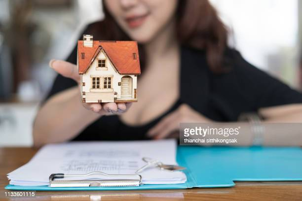 real estate concept; estate sale woman agent giving home model - real estate developer stock pictures, royalty-free photos & images