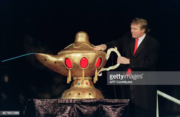Real estate developer Donald J Trump rubs a 'magic lamp' during the opening ceremony for his huge Taj Mahal casino in Atlantic city 05 April 1990...