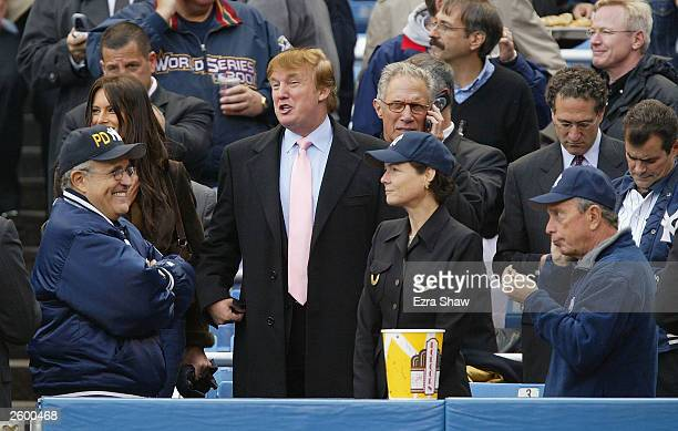 Real estate magnate Donald Trump talks with former New York City mayor Rudy Giuliani while current mayor Michael Bloomberg eats popcorn before the...
