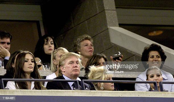 Real estate mogul Donald Trump watches Venus and Serena Williams compete during the women's final match of the US Open with his girlfriend Melania...