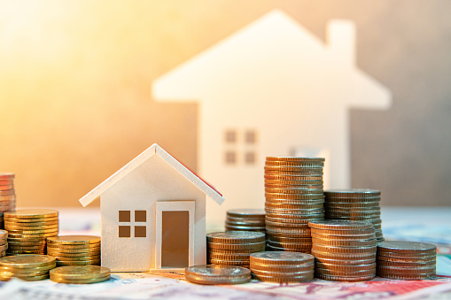 Real estate or property investment. Home mortgage loan rate. Saving money for retirement concept. Coin stack on international banknotes with house model on table. Business growth background 1019219898