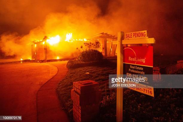 A real estate sign is seen in front of a burning home during the Carr fire in Redding California on July 27 2018 One firefighter has died and at...