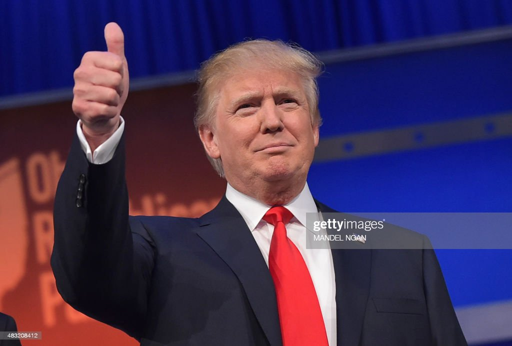Real estate tycoon Donald Trump flashes the thumbs-up as he arrives on stage for the start of the prime time Republican presidential debate on August 6, 2015 at the Quicken Loans Arena in Cleveland, Ohio. AFP PHOTO/MANDEL NGAN