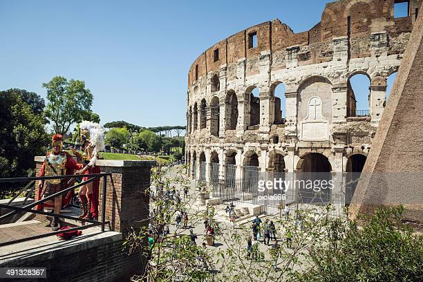 real fake gladiator entertaining tourists in front of the coliseum - roman stock photos and pictures