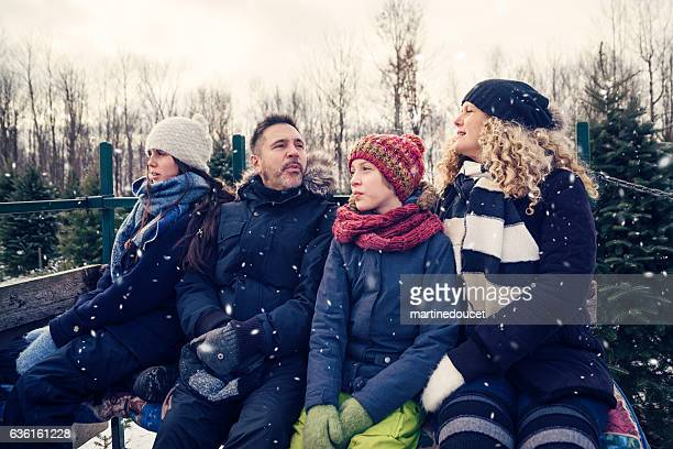 Real family in carriage enjoying leisure time outdoor in snow.