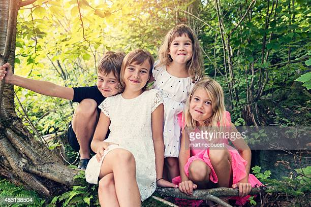 Real family of four kids posing together in summer nature.