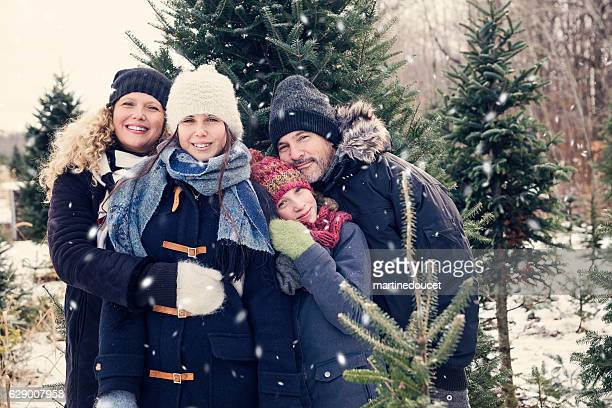 Real family portrait in winter with fir trees and snow.