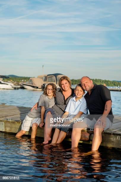 Riktig familj porträtt sitter på träpiren fötter i sjön.