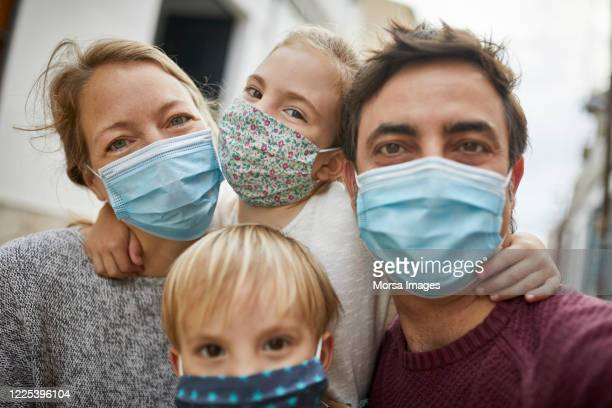 real family taking a selfie together while wearing protective face masks - abstand halten infektionsvermeidung stock-fotos und bilder