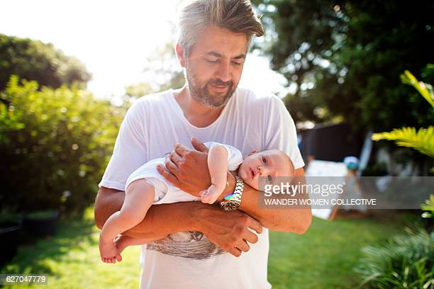 Real father holding baby in garden on sunny day