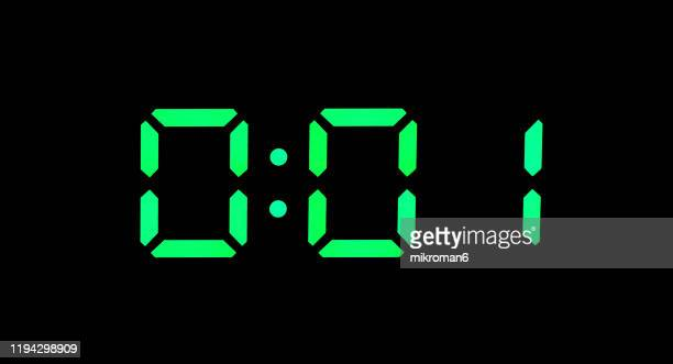real green led digital clock showing time 0:01 - midnight stock pictures, royalty-free photos & images