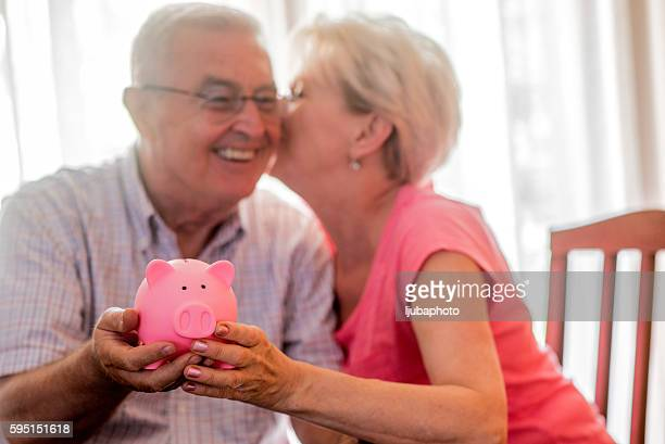 Real Happy senior couple with piggy bank