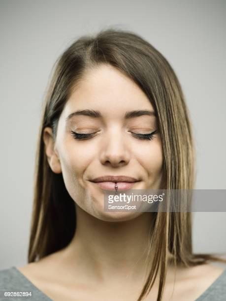 目を閉じての本当の幸せな若い女性スタジオ ポートレート